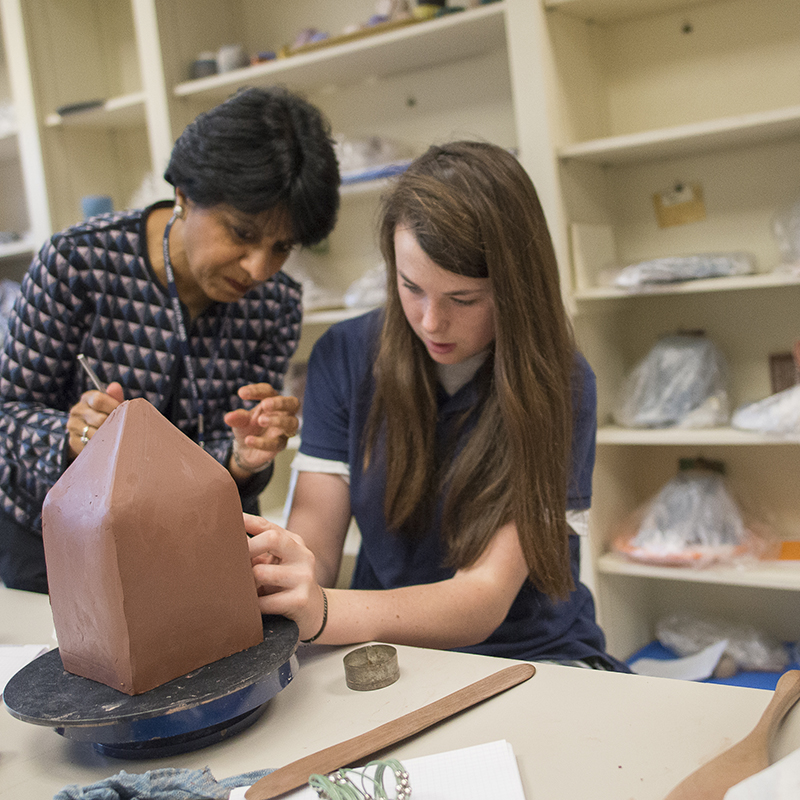 Upper School art student working with her teacher in ceramics class