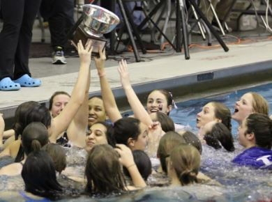 Swim team in the pool with championship cup celebrating