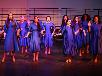 Upper School swing choir students singing on stage